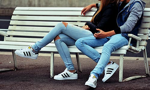 Man and woman sitting on bench wearing matching Adidas sneakers