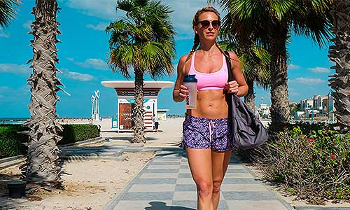 Woman carrying blender bottle and gym bag