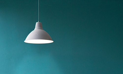 Pendant light hanging in front of a blue wall