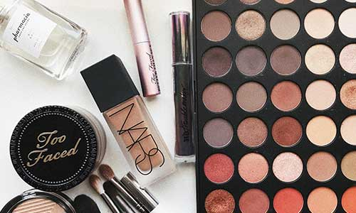 An eyeshadow palette, mascara, makeup brushes, and more makeup items spread out on a surface